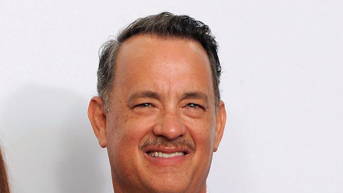 """FILE - This Sept. 23, 2012 file photo shows Tom Hanks backstage at the 64th Primetime Emmy Awards at the Nokia Theatre in Los Angeles. Hanks' Broadway debut will include an old buddy _ former """"Bosom Buddies"""" co-star Peter Scolari will share the stage with the Oscar winner. Producers revealed the rest of the cast to appear with Hanks in Nora Ephron's play """"Lucky Guy,"""" which begins previews March 1 at the Broadhurst Theatre. (Photo by Jordan Strauss/Invision/AP, file)"""