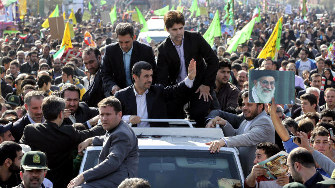 Escorted by his bodyguards, Iranian President Mahmoud Ahmadinejad, center, waves to well wishers from his car, during an annual rally commemorating the anniversary of the 1979 Islamic revolution, which toppled the late pro-U.S. Shah, Mohammad Reza Pahlavi, in Tehran, Iran, Sunday, Feb. 10, 2013. In his statements to the rally, Ahmadinejad said he is ready to have direct talks with United States if the West stops pressuring his country. (AP Photo/Vahid Salemi)