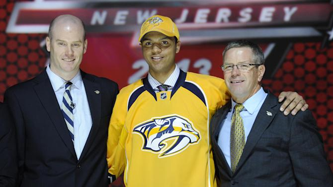 Seth Jones, a defenseman, stands with officials from the Nashville Predators sweater after being chosen 4th overall in the first round of the NHL hockey draft, Sunday, June 30, 2013, in Newark, N.J. (AP Photo/Bill Kostroun)