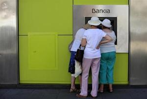 People use an ATM machine at a branch of Spain's nationalized lender Bankia in Seville