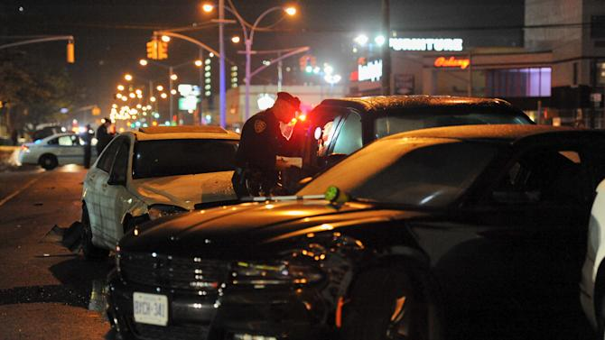 A New York City police officer inspects cars at a crash site in the Brooklyn borough in New York