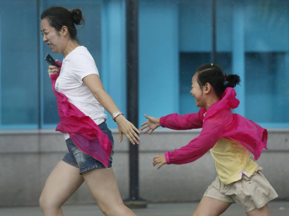 Tourists react to strong wind near the waterfront in Hong Kong Wednesday, Aug. 14, 2013. Typhoon Utor lashed Hong Kong with wind and rain, closing down the bustling Asian financial center Wednesday before sweeping toward mainland China. (AP Photo/Vincent Yu)