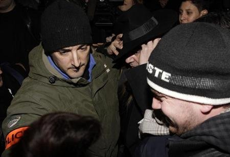 Fashion designer John Galliano surrounded by policemen leaves after a hearing in a police station in Paris February 28, 2011. REUTERS/Jacky Naegelen