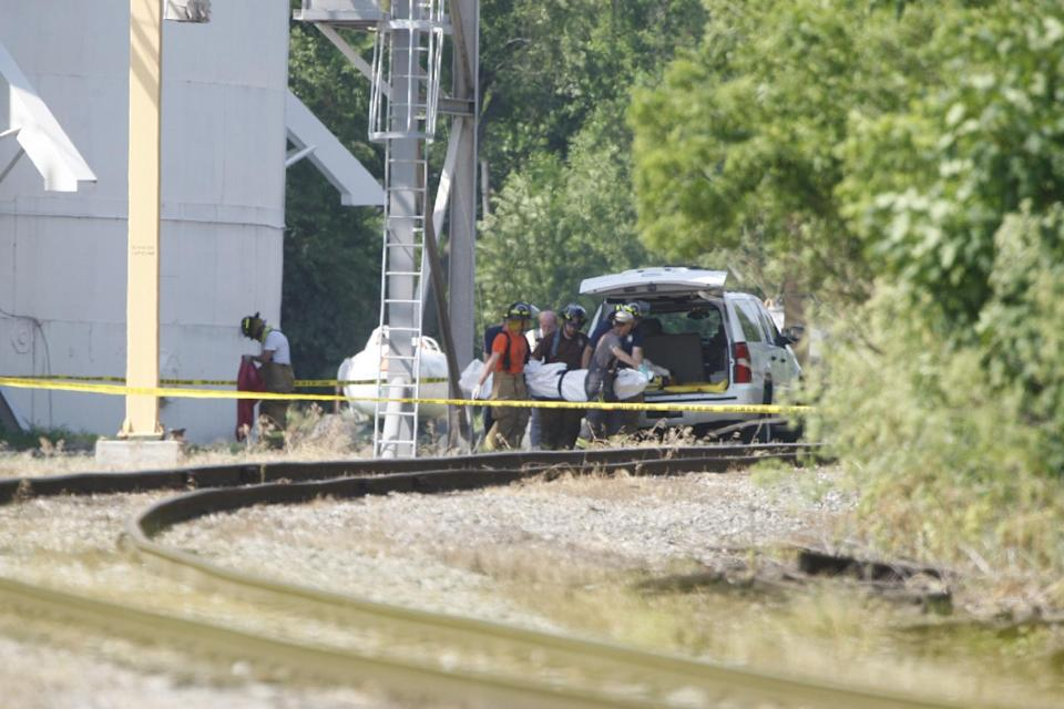 First responders remove a body following an explosion at a grain silo in Union Mills, Ind., on Monday, June 24, 2013. The victim was a co-op employee believed to be working in the silo when the blast happened, the LaPorte County Sheriff's department said. (AP Photo/South Bend Tribune, Robert Franklin)
