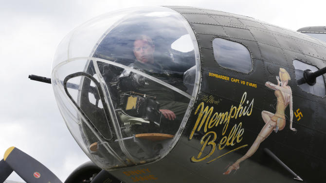 """King Co. Sheriff Deputy Guy Herndon inspects the front gun turret of a Boeing B-17 """"Flying Fortress"""" bomber Monday, May 5, 2014, as the plane sits parked in Renton, Wash., near Seattle. The recreated model of the """"Memphis Belle"""" World War II airplane will be available for paid rides and donation-based ground tours on May 10-11, 2014 at the Renton Municipal Airport in Renton, Wash. (AP Photo/Ted S. Warren)"""