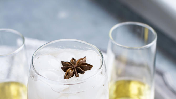 n this image taken on Jan. 28, 2013, a glass of spiced-rose pomegranate spritzer with a star anise on top, center, and two glasses of sparkling wine are shown on a serving tray in Concord, N.H. (AP Photo/Matthew Mead)