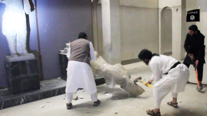 In this image made from video posted on a social media account affiliated with the Islamic State group on Thursday, Feb. 26, 2015, which has been verified and is consistent with other AP reporting, militants take sledgehammers to an ancient artifact in the Ninevah Museum in Mosul, Iraq. The extremist group has destroyed a number of shrines --including Muslim holy sites -- in order to eliminate what it views as heresy. The militants are also believed to have sold ancient artifacts on the black market in order to finance their bloody campaign across the region. (AP Photo via militant social media account)