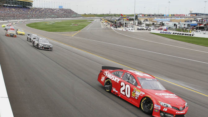 FILE - In this April 21, 2013 file photo, Matt Kenseth (20) leads into a turn during a NASCAR Sprint Cup race at Kansas Speedway in Kansas City, Kan. Kenseth's race-winning car from Kansas failed inspection at NASCAR's Research and Development Center, The Associated Press has learned. NASCAR officials were discussing Wednesday, April 24, 2013 what penalties to levy against Kenseth and Joe Gibbs Racing, multiple people familiar with the inspection told the AP on the condition of anonymity because no decision has been made. (AP Photo/Colin E. Braley, File)