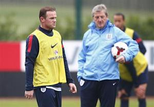 England national team soccer player Rooney walks past manager Hodgson during a team training session in London Colney