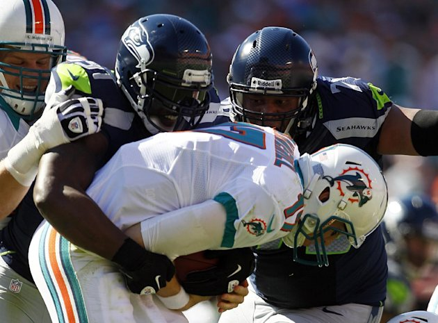 Seattle Seahawks defensive end Chris Clemons (91), left, and  Red Bryant (79) sack Miami Dolphins quarterback Ryan Tannehill (17) during the first half of an NFL football game on Sunday, Nov. 25, 2012