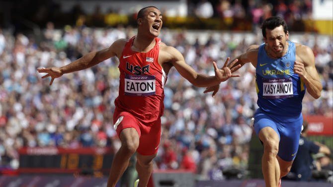 United States' Ashton Eaton, left, and Ukraine's Voleksiy Kasyanov, right, cross the finish line in a men's decathlon 100-meter heat during the athletics in the Olympic Stadium at the 2012 Summer Olympics, London, Wednesday, Aug. 8, 2012. (AP Photo/Anja Niedringhaus)