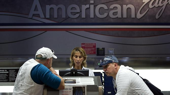 FILE- In this Friday, Oct. 5, 2012, file photo, two unidentified American Airlines passengers talk to a customer service representative, center in Miami. Just weeks ago, American Airlines was working its way through bankruptcy court, on schedule for one of the fastest turnarounds in aviation history, but then, domestic traffic fell by 7.1 percent in September from the same month a year earlier. No other major airline experienced a drop like that. (AP Photo/J Pat Carter, File)
