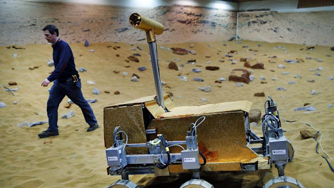 "Engineer Ben Nye walks past a robotic vehicle on the 'Mars Yard Test Area', a testing ground for the robotic vehicles of the European Space Agency's ExoMars program scheduled for 2018, in Stevenage, England, Thursday, March 27, 2014. It looks like a giant sandbox - except the sand has a reddish tint and the ""toys"" on display are very expensive prototypes designed to withstand the rigors of landing on Mars. The scientists here work on the development of the autonomous navigation capabilities of the vehicle, so by being in communication with controllers on earth twice a day, will be able to use the transmitted information to navigate to new destinations on Mars. (AP Photo/Lefteris Pitarakis)"