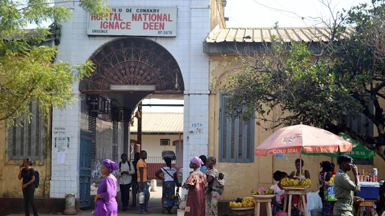 People walk in front of the Ignace Deen hospital in Conakry on March 27, 2014