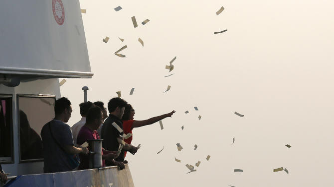 Relatives of the victims throw fake money Tuesday, Oct. 2, 2012 to pay tribute to the ill-fated people aboard a boat that sank Monday night near Lamma Island, off the southwestern coast of Hong Kong Island. The boat packed with revelers on a long holiday weekend collided with a ferry and sank off Hong Kong, killing at least 36 people and injuring dozens, authorities said.  (AP Photo/Vincent Yu)