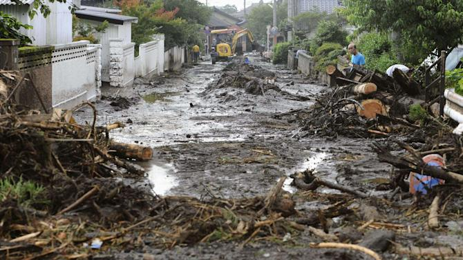 A road is covered with mud and woods carried by a mudslide in Aso, Kumamoto Prefecture, western Japan, Thursday, July 12, 2012. Heavy rains hit southern Japan, triggering flashfloods, mudslides and destroying dozens of homes. (AP Photo/Kyodo News) JAPAN OUT, MANDATORY CREDIT, NO LICENSING IN JAPAN, CHINA, HONG KONG, SOUTH KOREA AND FRANCE