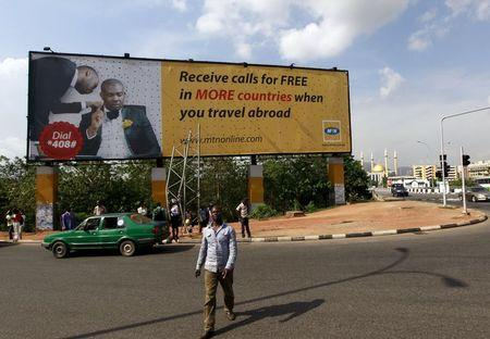 Man walks in front of an advertisement billboard of MTN phone company in Abuja, Nigeria