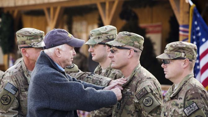 U.S. Senator John McCain pins medals on soldiers during a Christmas day visit on forward operating base Gamberi in the Laghman province of Afghanistan