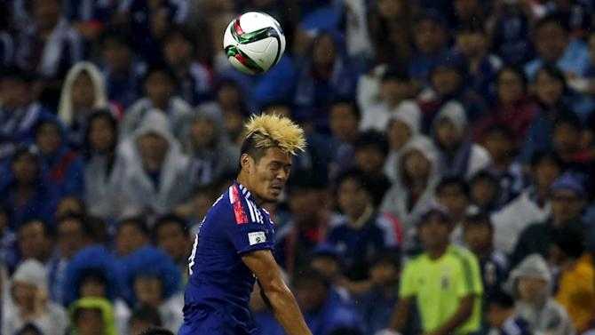 Japan's Yamaguchi fights for the ball with Cambodia's Tit as Japan's Nagatomo looks on during their 2018 World Cup qualifying soccer match at Saitama Stadium in Saitama