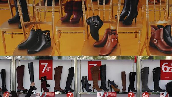 A customer picks up a shoe at a shop where posters advertising price discounts are hung, outside a department store in Beijing