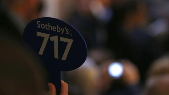 Buyer raises a bid during the sale of jewellery at Sotheby's in Geneva