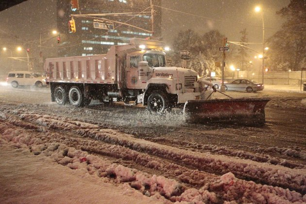 Sanitation workers shovel snow from Queens Blvd. during a snow storm Wednesday, Nov. 7, 2012, in New York. Coastal residents of New York and New Jersey faced new warnings to evacuate their homes and a