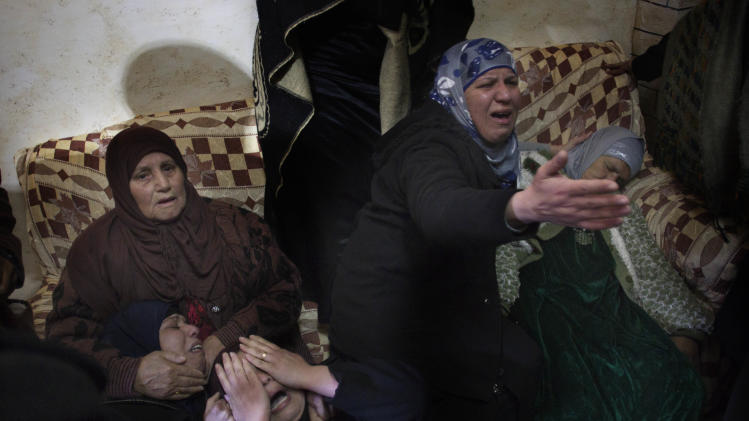 Relatives of  Palestinian Talat Ramia mourn during his funeral in the West Bank town of Al-Ram, near Jerusalem, Saturday, Feb. 25, 2012. On Friday Ramia was shot dead by Israeli forces while throwing fire crackers at them. (AP photo/Bernat Armangue)