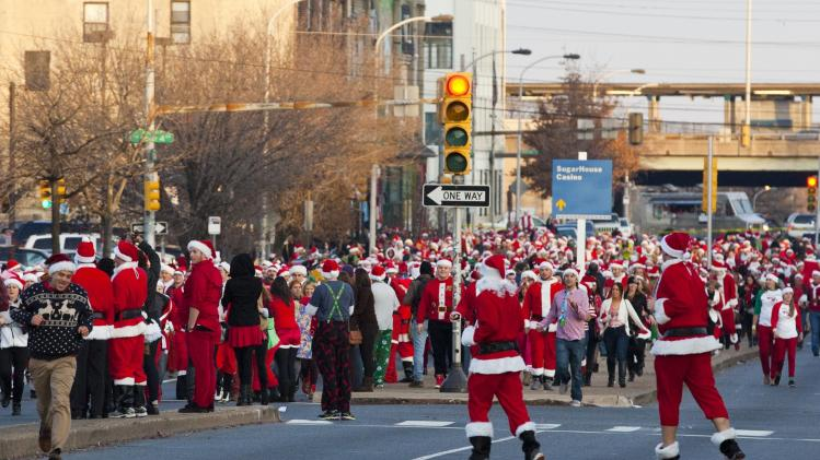 Participants in the Running of the Santas Festival run along Spring Garden street before a rock music concert at The Electric Factory in Philadelphia, Pennsylvania
