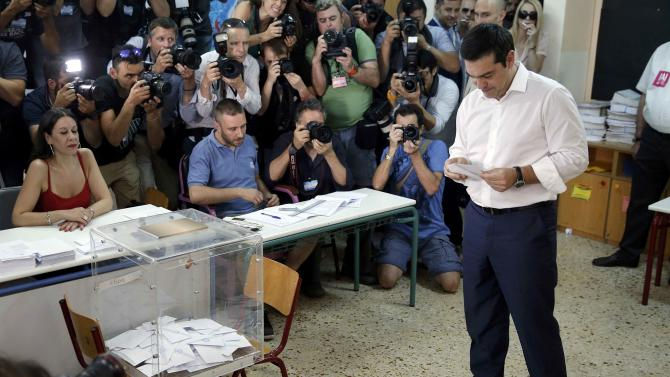 Greek Prime Minister Alexis Tsipras looks at his ballot before voting in national referendum at a polling station in Athens