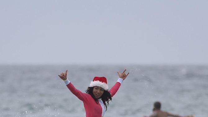 British traveler Dabriella Quayle rides the waves while celebrating Christmas Day at Bondi Beach in Sydney, Thursday, Dec. 25, 2014. (AP Photo/Rick Rycroft)