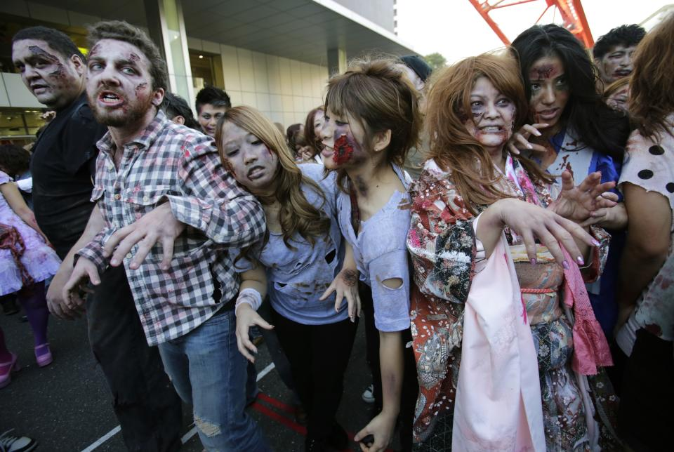 Former sumo grand champion Akebono, far left, and other participants wearing zombie makeups, perform during a Halloween event at Tokyo Tower in Tokyo, Thursday, Oct. 31, 2013. (AP Photo/Shizuo Kambayashi)