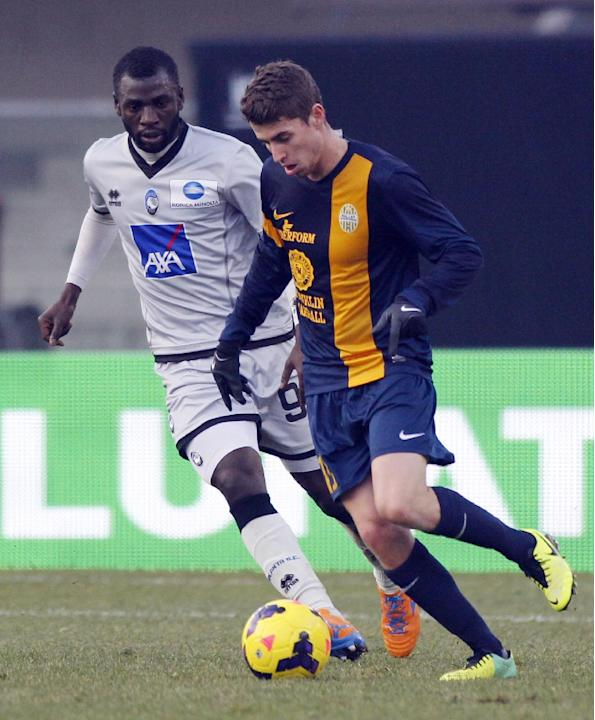 Atalanta's Moussa Kone, left, of Ivory Coast, challenges Hellas Verona Brazilian midfielder Jorginho during a Serie A soccer match at Bentegodi stadium in Verona, Italy, Sunday, Dec. 8, 2013