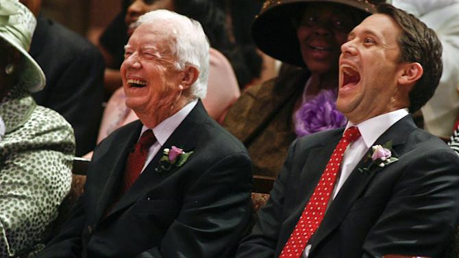 Former President Jimmy Carter, left, and his grandson, Georgia Democratic candidate for governor Jason Carter, react to a joke from the pulpit Sunday, Oct. 12, 2014 at Mt. Zion Baptist Church in Albany, Ga. After an absence of four decades, the former president is returning to the campaign trail this year on behalf of Jason Carter, who's challenging incumbent Republican Gov. Nathan Deal. (AP Photo/Phil Sears)