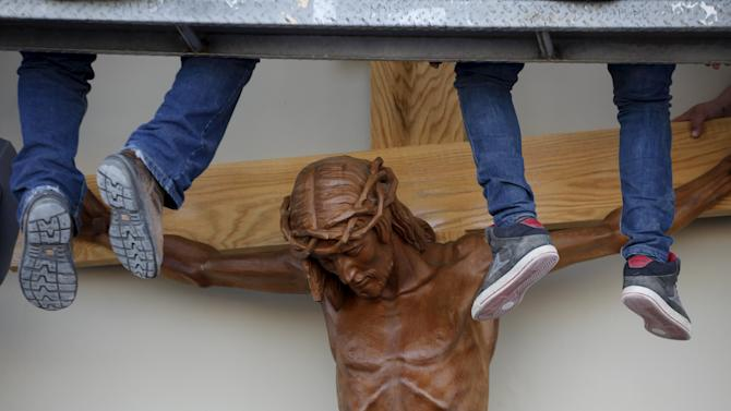 Workers put up a figure of Jesus Christ at the border between Mexico and the U.S. in Ciudad Juarez