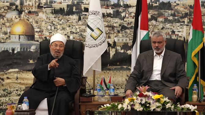 "Influential Muslim cleric Yusuf al-Qaradawi, left, talks as Gaza's Hamas Prime Minister Ismail Haniyeh listens, during their meeting in Gaza City, Thursday, May 9, 2013. al-Qaradawi has declared that Israel has no right to exist on Thursday and said that ""this land has never once been a Jewish land. Palestine is for the Arab Islamic nation."" The Qatar-based cleric hosts a popular TV show and is widely respected in the Muslim world. (AP Photo/Adel Hana)"