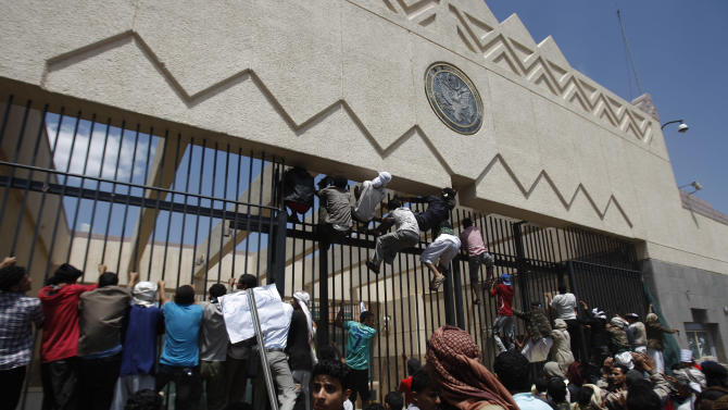"""Yemeni protesters climb the gate of the U.S. Embassy during a protest about a film ridiculing Islam's Prophet Muhammad, in Sanaa, Yemen, Thursday, Sept. 13, 2012. Dozens of protesters gather in front of the US Embassy in Sanaa to protest against the American film """"The Innocence of Muslims"""" deemed blasphemous and Islamophobic. (AP Photo/Hani Mohammed)"""