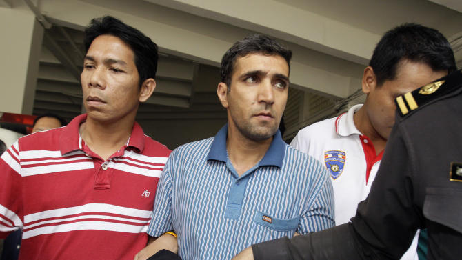 FILE - In this Thursday, Feb. 16, 2012 file photo, Thai immigration officers escort detained Iranian Mohammad Kharzei, center, at the immigration headquarters in Bangkok, Thailand. In Bangkok, the three Iranian suspects in custody appeared to take advantage of Thailand's foreigner-friendly culture to live openly while allegedly putting together a bomb cache whose targets, police say, included the Israeli Embassy.(AP Photo/Sakchai Lalit, File)