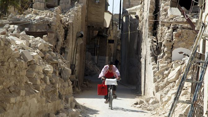 A man rides a bicycle through a damaged street in Old Aleppo, Syria