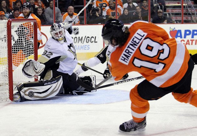 Philadelphia Flyers' Scott Hartnell, right, takes a wrist shot at Pittsburgh Penguins goalie Tomas Vokoun who deflected the puck in the second period of an NHL hockey game, Thursday, March 7, 2013, in