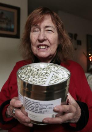 Elvy Musikka, 72, who suffers from glaucoma, shows the canister holding marijuana cigarettes she regularly receives from the U.S. Government in Eugene, Ore., Tuesday, Sept. 27, 2011. For the past three decades, the federal government has been providing a handful of patients with some of the highest grade marijuana around. The program grew out of a 1976 court settlement that created the country's first legal pot smoker. (AP Photo/Don Ryan)