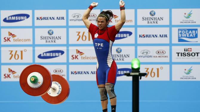 Taiwan's Hsu celebrates after breaking the world record for the women's 53kg weightlifting competition after lifting a combined total of 233kg during the 17th Asian Games in Incheon