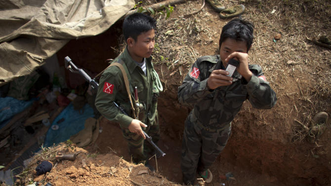 A Kachin Independence Army (KIA) soldier uses his mobile phone while another watches as they stand near a gas mask, bottom left, in their newly-dug trench at an outpost a mile away from a hill top ceased by Myanmar's government troops, five miles away from the town of Laiza, in Northern Myanmar's Kachin-controlled region, Tuesday, Jan. 29, 2013. A key outpost protecting the headquarters of ethnic Kachin rebels in northern Myanmar has fallen to government troops, a spokesman for the guerrilla group said Sunday. The Kachin Independence Army spokesman said the hillside outpost at Hka Ya Bhum, near the guerrilla group's headquarters in the town of Laiza, was overrun Saturday afternoon. (AP Photo/Alexander F. Yuan)