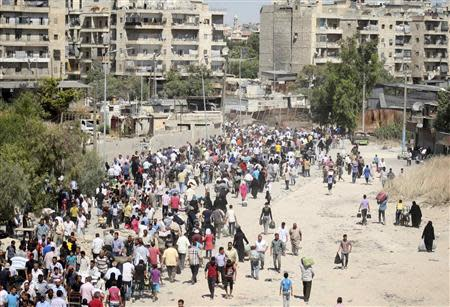 A view is seen of civilians as they walk at the Karaj al-Hajez crossing, a passageway separating Aleppo's Bustan al-Qasr, which is under the rebels' control and Al-Masharqa neighborhood