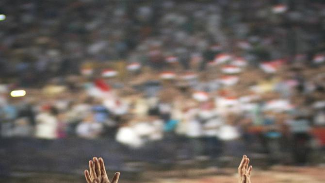 Egyptian President Mohammed Morsi, waves to the crowd gathered in a stadium upon his arrival for a speech on the 6th of October national holiday marking the 1973 war with Israel, Cairo, Egypt, Saturday, Oct. 6, 2012.(AP Photo/Khalil Hamra)