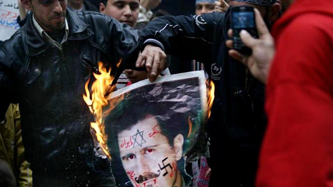 """In this Monday March 25, 2013, citizen journalism image provided by Aleppo Media Center AMC which has been authenticated based on its contents and other AP reporting, anti-Syrian regime protesters burn a portrait for Syrian President Bashar Assad during a protest, in Aleppo, Syria. Syrian activists say government forces have seized control of a neighborhood in the central city of Homs that is a symbol of opposition to President Bashar Assad's regime. The Arabic on the poster reads, the dog of Iran, devil's party (Hezbollah)."""" (AP Photo/Aleppo Media Center, AMC)"""