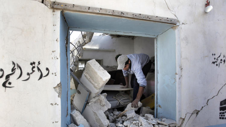 A Syrian man searches through rubble of his home, which was destroyed from a Syrian government airstrike earlier in the day, in Marea village, on the outskirts of Aleppo, Syria, Sunday Sept. 23, 2012. Syria's bloody 18-month conflict, which activists say has killed nearly 30,000 people, has so far eluded all attempts at international mediation. (AP Photo/Hussein Malla)
