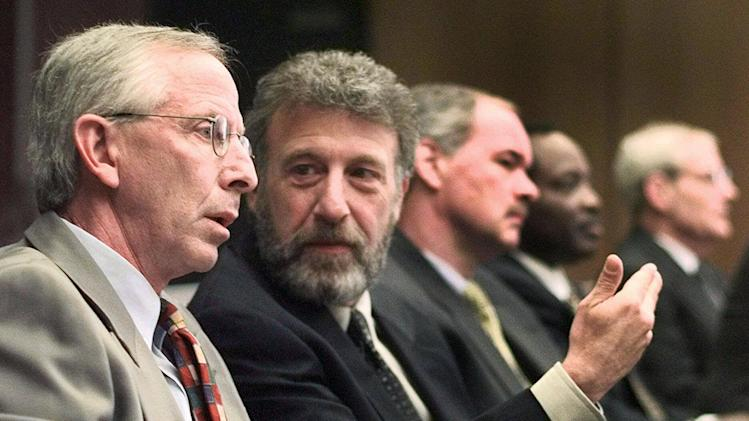 FILE - In this Thursday, May 6, 1999 file photo, George Zimmer, second from left, gestures to Andy Dolich prior to a meeting, in Oakland, Calif. Men's Wearhouse Inc. says it has dismissed Zimmer, its founder and executive chairman. In a terse release issued Wednesday, June 19, 2013, the company didn't give a reason for the abrupt firing of Zimmer, who built Men's Wearhouse from one small Texas store using a cigar box as a cash register to one of the nation's largest specialty retailers in men's clothing, with 1,143 locations. (AP Photo/Ben Margot, File)