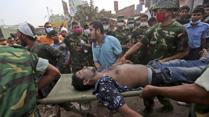 A Bangladeshi garment worker who was pulled alive from the rubble is rushed on a stretcher at the site of a building that collapsed Wednesday in Savar, near Dhaka, Bangladesh, Friday, April 26, 2013. The death toll reached hundreds of people as rescuers continued to search for injured and missing, after a huge section of an eight-story building that housed several garment factories splintered into a pile of concrete.(AP Photo/Kevin Frayer)