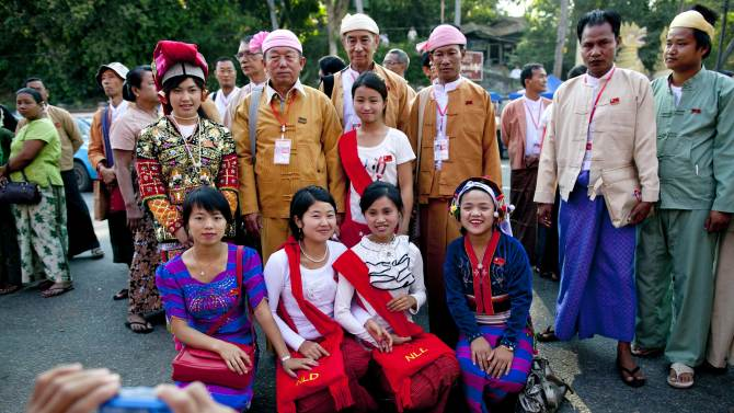 """Ethnic Shan representatives of Aung San Suu Kyi's National League for Democracy, with badges around their necks, pose for photos with women dressed in ethnic attire outside the venue of first ever NLD party congress in Yangon, Myanmar, Friday, March 8, 2013. Nearly 900 representatives from across the country stood in neat lines outside the Taw Win (""""Royal Rose"""") restaurant, waiting to be screened for entry to elect their party leadership for the first time in the NLD's 25-year history. (AP Photo/Gemunu Amarasinghe)"""