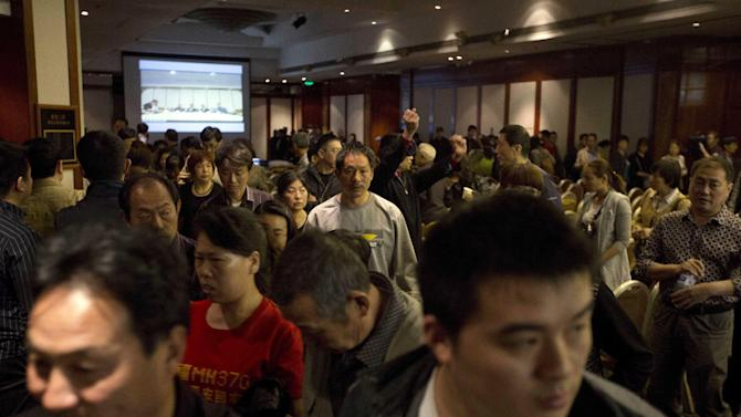 Relatives of Chinese passengers on board the missing Malaysia Airlines 370 walk out from a video-conference with Malaysian officials in protest at the difficulties of communications in Beijing, China, Wednesday, April 16, 2014. A robotic submarine looking for the lost Malaysian jet continued its second seabed search on Wednesday as up to 14 planes were to take to the skies for some of the final sweeps of the Indian Ocean for floating debris from the ill-fated airliner. (AP Photo/Ng Han Guan)